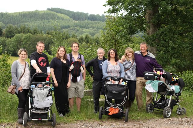 Parents with babies stand on a track surrounded by hedges and fields.
